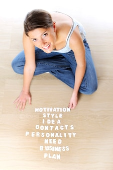 Een jonge vrouw die op de grond zit en een businessplan maakt