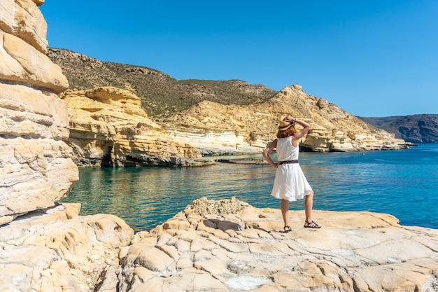 Een jonge vrouw die op een mooie zomerdag naar de zee kijkt in rodalquilar in cabo de gata, almería