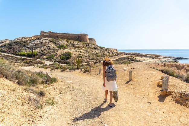 Een jonge vrouw die op een mooie zomerdag naast het rodalquilar-kasteel in cabo de gata loopt, almería
