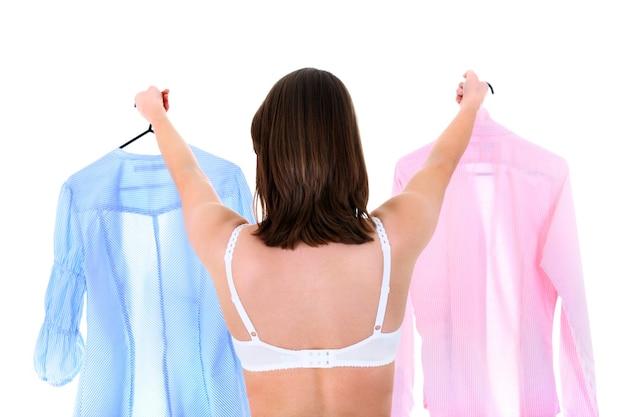 Een jonge vrouw die probeert te kiezen tussen twee witte overhemden