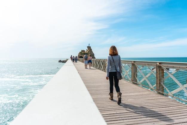 Een jonge vrouw die samen over de houten brug wandelt in plage du port vieux in biarritz, op vakantie in het zuidoosten van frankrijk