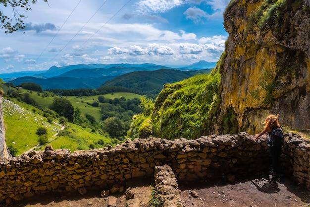 Een jonge vrouw die uitkijkt vanuit de grot van san adrian. mount aizkorri 1523 meter, de hoogste in guipuzcoa. baskenland. klim door san adrian en keer terug door de oltza-velden