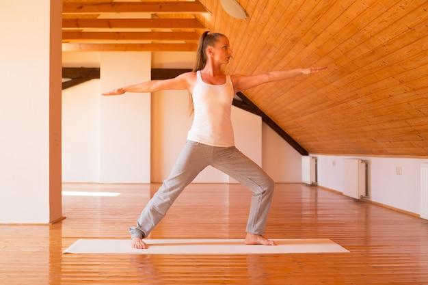 Een jonge vrouw die yoga beoefent in een grote zolderstudio.