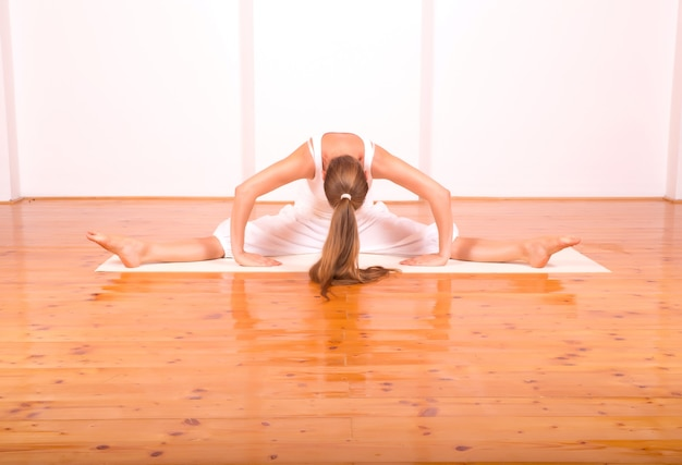 Een jonge vrouw die yoga beoefent in een zolderstudio.