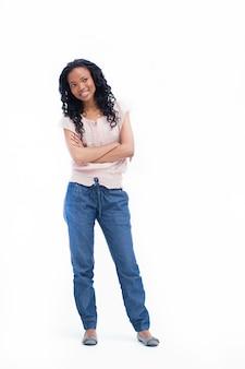 Een jonge vrouw die zich met haar gevouwen wapens bevindt glimlacht