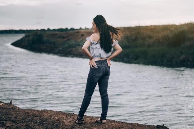Een jonge vrouw die zich omdraait in een glimlach. een mooie toeristenvrouw geniet 's avonds van de rivier en de zonsondergang