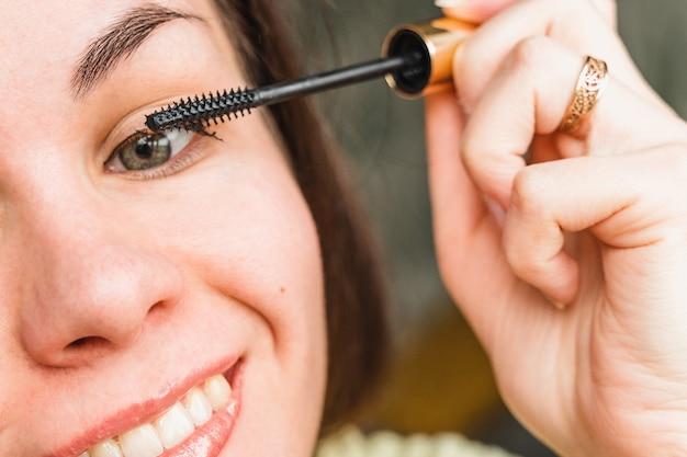 Een jonge vrouw doet make-up meisje schildert haar wimpers met mascara