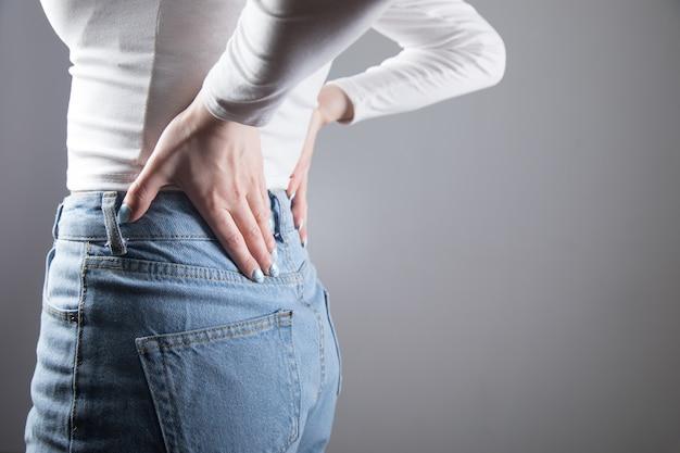 Een jonge vrouw doet nieren pijn in een grijze scène Premium Foto