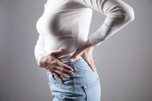 Een jonge vrouw doet nieren pijn in een grijze scène