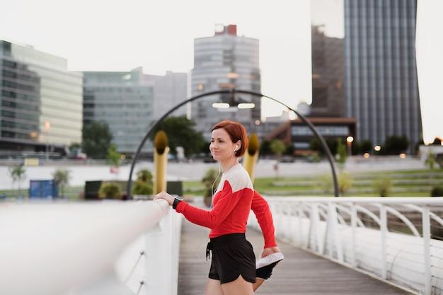 Een jonge vrouw doet oefening op brug buiten in de stad, die zich uitstrekt.