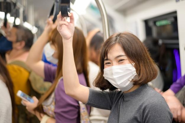 Een jonge vrouw draagt een beschermend masker in de metro, covid-19 bescherming, veiligheidsreizen, nieuw normaal, sociaal afstand nemen, veiligheidstransport, reizen onder pandemisch concept.