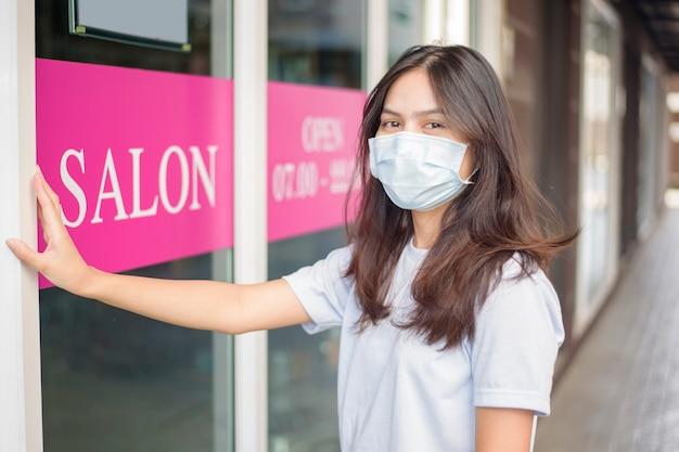 Een jonge vrouw draagt gezichtsmasker ter bescherming covid-19 staande voor schoonheidssalon
