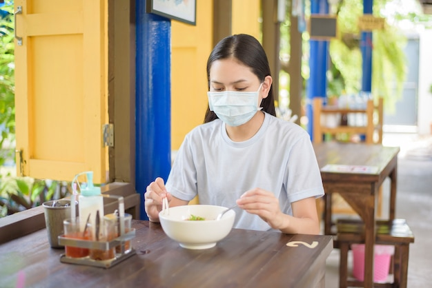 Een jonge vrouw eet thais straatvoedsel, draagt gezichtsmasker, nieuw normaal het eten concept