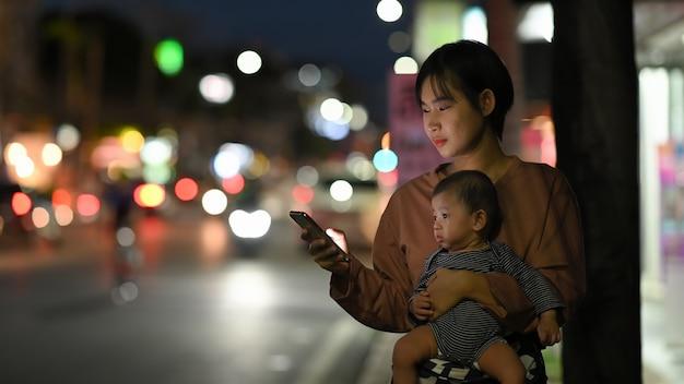 Een jonge vrouw en een baby wachten op haar privétaxi terwijl ze een transport-app op een mobiele telefoon gebruiken