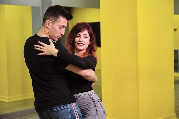 Een jonge vrouw en een man die salsa en bachata onderwijst