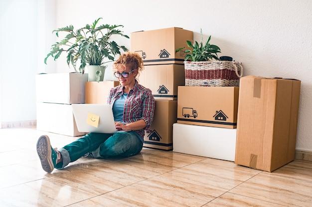 Een jonge vrouw en gelukkige mensen hebben na het kopen van een nieuw huis of appartement samen een nieuw huis of appartement gekocht om samen te wonen - persoon op de grond die een laptop gebruikt met dozen-advertentiepakketten op hun rug