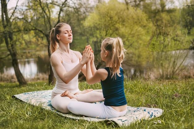 Een jonge vrouw en haar dochter beoefenen yoga in de frisse lucht