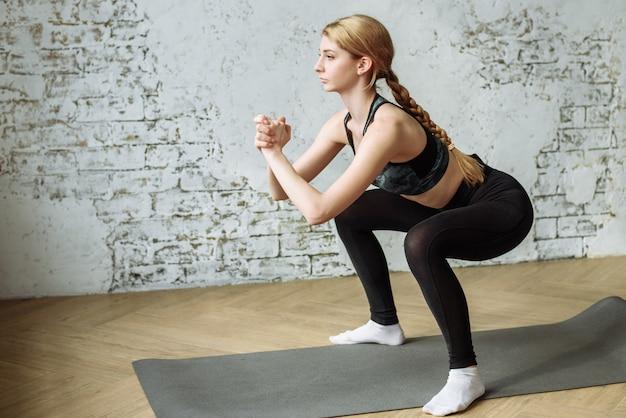 Een jonge vrouw gaat tijdens de quarantaine thuis sporten en brengt haar lichaam in vorm