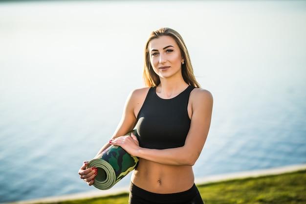 Een jonge vrouw gaat voor haar training op het strand met yogamat. buitenshuis.