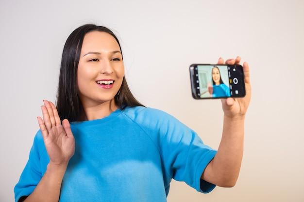 Een jonge vrouw gebruikt een smartphonecamera op een crèmeachtergrond.