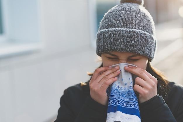 Een jonge vrouw gebruikt een zakdoek tijdens een loopneus