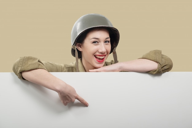 Een jonge vrouw, gekleed in amerikaanse ww2 militair uniform met lege leeg bord
