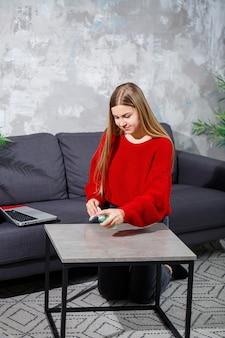 Een jonge vrouw gekleed in een rode gebreide trui doet thuis de schoonmaak, ze stoft de tafel af.