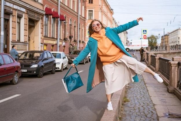 Een jonge vrouw, gekleed in herfstkleren en zonnebril, loopt vrolijk door de straten van de stad. wandelen concept.