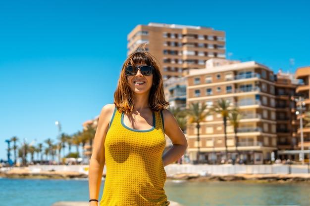 Een jonge vrouw gekleed in het geel geniet van de vakantie in de kustplaats torrevieja, alicante, valenciaanse gemeenschap