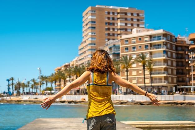 Een jonge vrouw geniet van de vakantie in de kustplaats torrevieja, alicante, valenciaanse gemeenschap