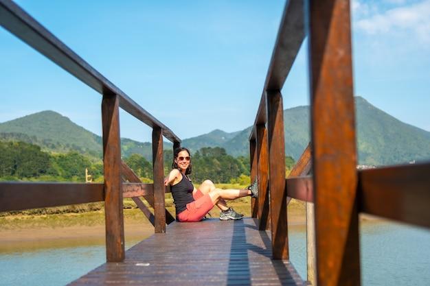 Een jonge vrouw geniet van het landschap vanaf de houten pieren van de urdaibai-moerassen, een biosfeerreservaat in bizkaia naast mundaka. baskenland
