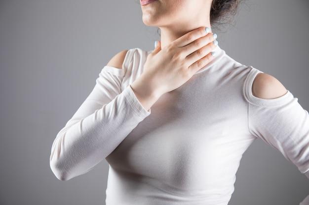 Een jonge vrouw heeft keelpijn op een grijze scène