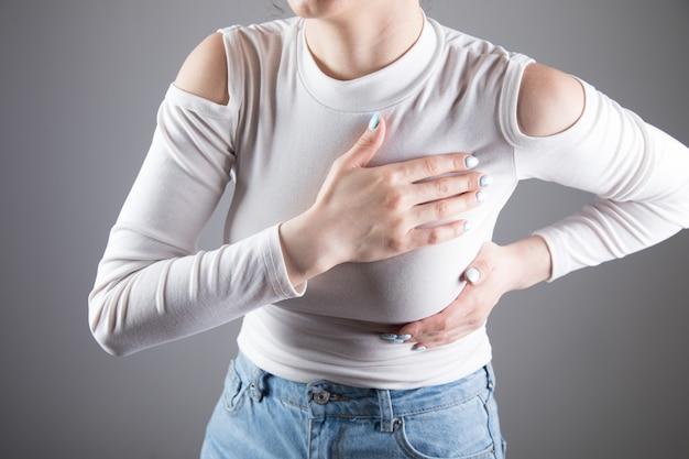 Een jonge vrouw heeft pijn op de borst op een grijze scène
