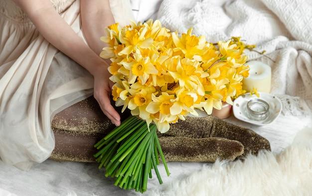 Een jonge vrouw houdt een boeket van narcissen. het concept van de lente en bloei.