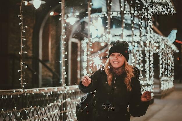 Een jonge vrouw houdt een sterretje in haar handen op de achtergrond van blauwe wazige bokehlichten