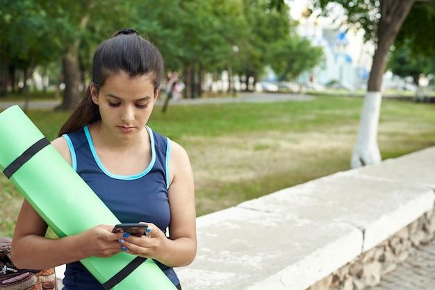 Een jonge vrouw houdt een yogamat vast en klimt aan de telefoon na een training op straat.