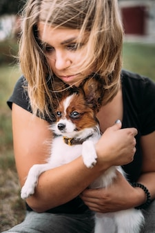 Een jonge vrouw houdt in haar armen een kleine witte en bruine kop van puppypapillon.