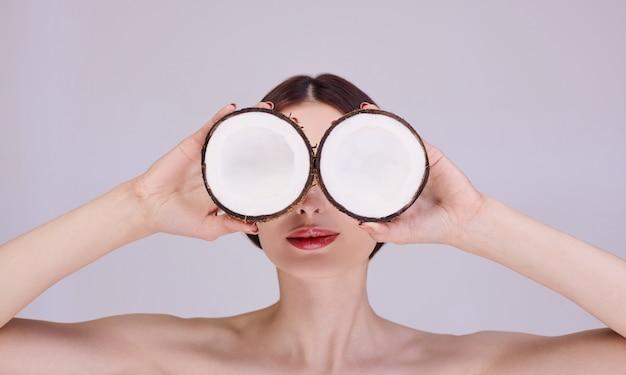 Een jonge vrouw houdt kokosnoten in haar handen als een bril.