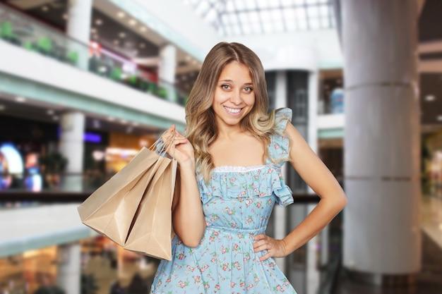 Een jonge vrouw houdt papieren ecotassen in haar hand op een wazige achtergrond van het winkelcentrum winkelmode