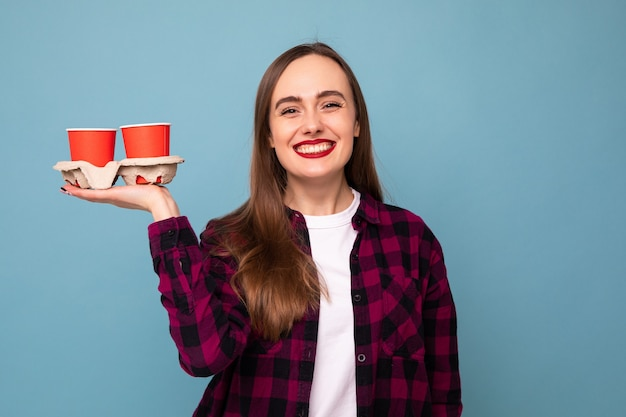 Een jonge vrouw houdt twee koffie in papieren bekertjes op een blauwe achtergrond