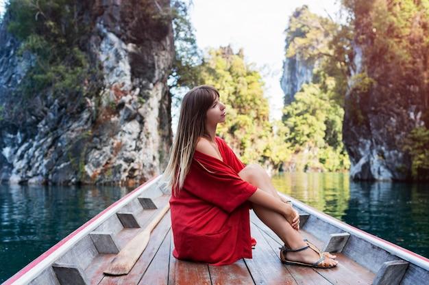 Een jonge vrouw in bikini zit op een kleine boot bij een tropisch eiland. zomervakantie.