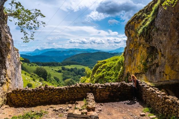 Een jonge vrouw in de grot van san adrian. mount aizkorri 1523 meter, de hoogste in guipuzcoa. baskenland. klim door san adrian en keer terug door de oltza-velden