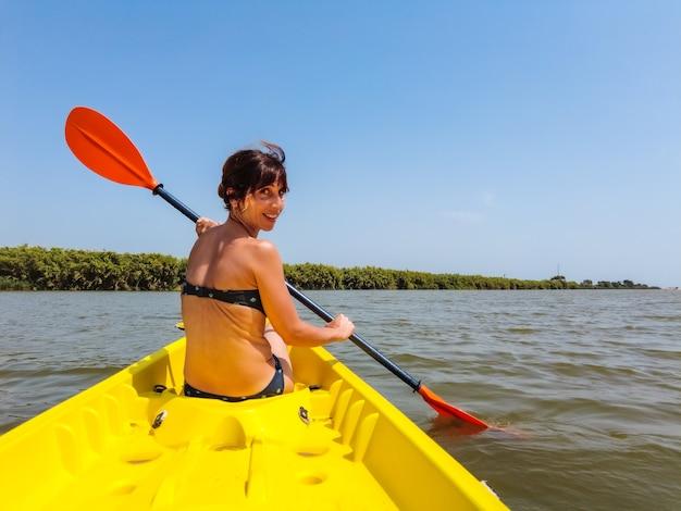 Een jonge vrouw in de kano kanoën in een natuurpark in catalonië, een rivier naast het strand in estartit