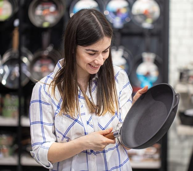 Een jonge vrouw in de winkel kiest een koekenpan. het concept van winkelen voor een huis.
