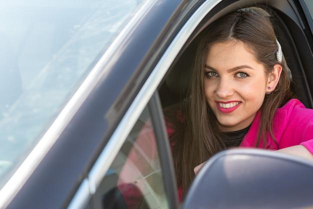 Een jonge vrouw in een auto zit en kijkt uit het raam