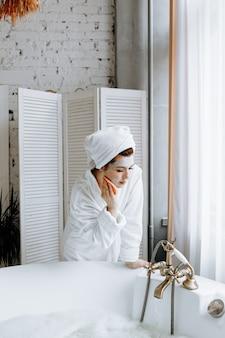 Een jonge vrouw in een badjas met een handdoek om haar hoofd gespoeld, wast een gezichtsmasker in de badkamer af.