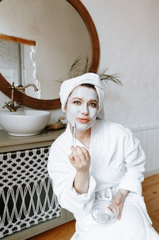 Een jonge vrouw in een badjas met een handdoek om haar hoofd gewikkeld, brengt een gezichtsmasker aan in de badkamer.