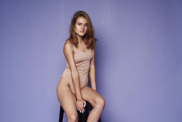 Een jonge vrouw in een beige bodysuit zit op een kubus op een paarse achtergrond. zomer, mode, stijl en beauty concept. ruimte kopiëren.