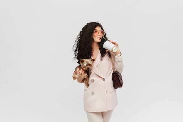 Een jonge vrouw in een beige pak yorkie terriër in de hand houden en een kopje koffie drinken