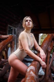 Een jonge vrouw in een beige zwempak staat op de trap. een meisje gaat naar boven naar het terras. het meisje heeft een mooi figuur